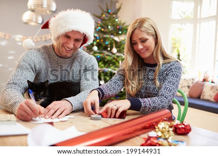 Couple Wrapping Christmas Gifts At Home - stock photo