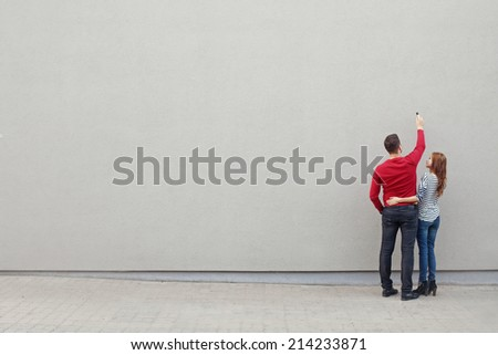 couple writing something on a blank wall - stock photo