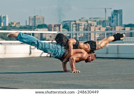 Couple yoga of woman and man on the house-top - stock photo