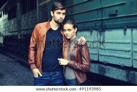 Couple. Young man and woman in leather jackets and jeans standing near the train