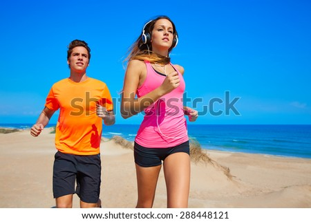 Couple young running in the beach in summer vacations - stock photo