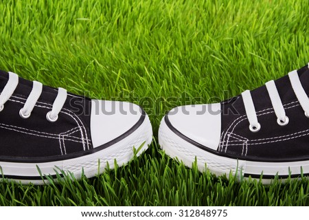 Couple youth sneakers, black and white sneakers, shoes on the green grass, outing, footwear close-up, green lawn, shoes for youth, sports shoes on the green grass. - stock photo