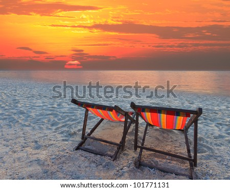 couples chairs beach at sea side and sun set - stock photo