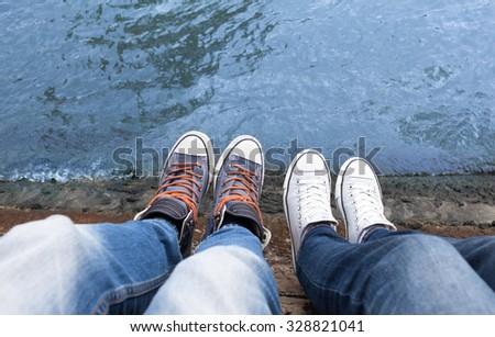 Couples feet relaxing on a bridge. - stock photo