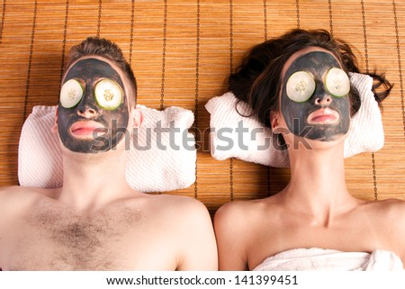 Couples holiday retreat at spa getting facial mask with cucumber skincare relaxing beauty treatment on bamboo. - stock photo