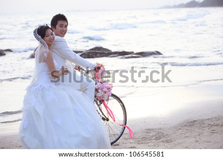 couples of groom and bride riding a bicycle on beach - stock photo