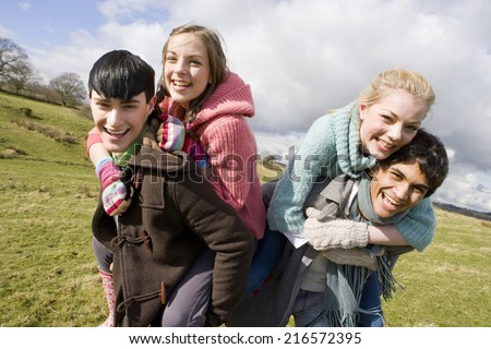 Couples piggybacking in sunny, rural field - stock photo