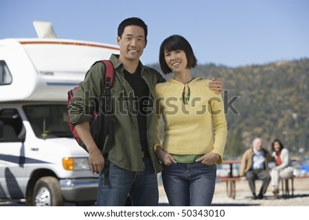 Couples standing in front of RV at lake - stock photo