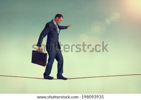 courageous businessman balancing on a tightrope or highwire