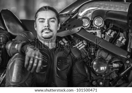 Courageous rider sits beside his motorcycle.