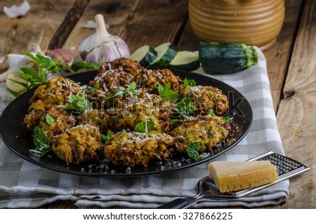 Courgette and Mint Fritters, very simple, very nice and delicious vegetarian food, sprinkled with herbs and parmesan - stock photo
