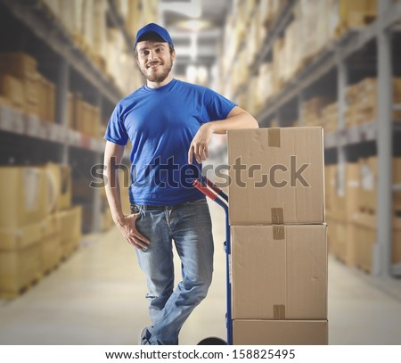 Courier at work with stack of boxes - stock photo