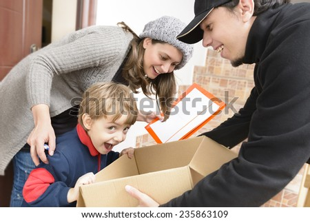 Courier Delivering a Package to a happy boy - stock photo