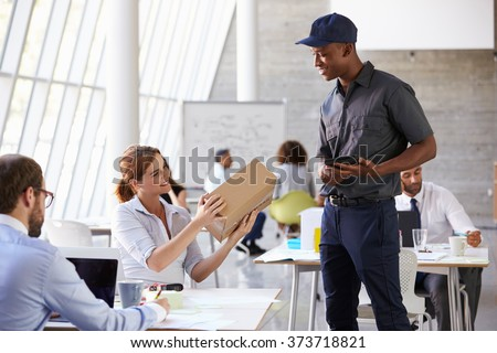 Courier Delivering Package To Businesswoman In Busy Office - stock photo