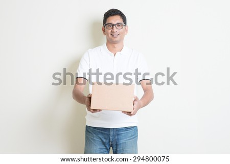 Courier delivery service concept. Indian man received a brown box, standing on plain background with shadow. Asian handsome guy model.  - stock photo