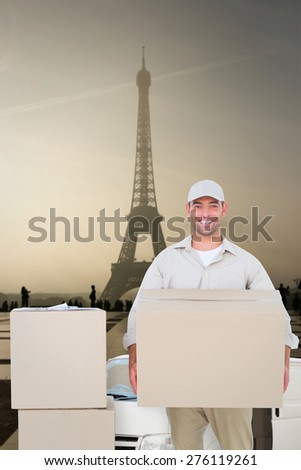 Courier man carrying cardboard box against eiffel tower - stock photo