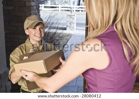 Courier or delivery driver delivering package to a woman at home - stock photo