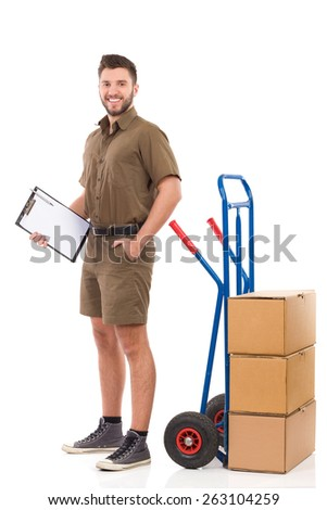 Courier waiting with a clipboard. Happy delivery man or mover standing with hand in pocket and holding a clipboard. Full length studio shot isolated on white. - stock photo