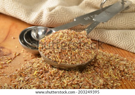 Course ground organic flax seed in a measuring spoon, shallow depth of field, focus on spoon. - stock photo