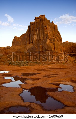 Courthouse Towers reflecting in puddle of water after a storm in Arches National Park. - stock photo