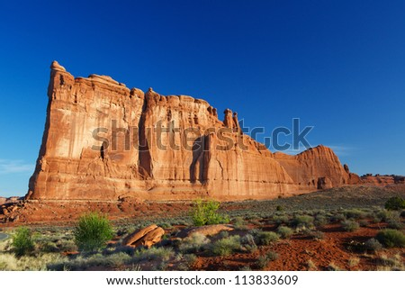 Courthouse Towers Ridge in Arches National Park with dramatic Blue Sky from distance - stock photo