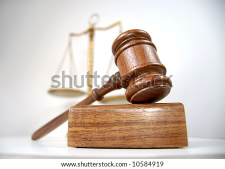 Courtroom detail with a gavel and scales of justice in the background - stock photo