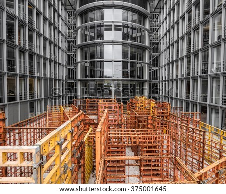 Courtyard cluttered by scaffolding inside modern office building in hi tech style - stock photo