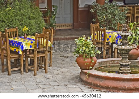 Courtyard mexican restaurant with a fountain and colorful tables - stock photo
