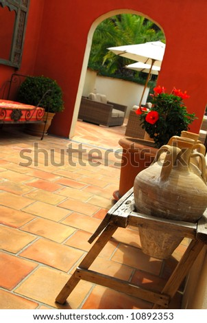 Courtyard of mediterranean villa in French Riviera. Shallow depths of filed, focus on amphoras. - stock photo