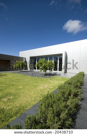 Courtyard of modern building with grass and trees - stock photo