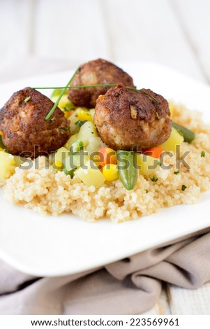 Couscous and meat balls with vegetables in the plate,selective focus. - stock photo
