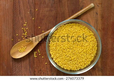 couscous in bowl on brown background and spoon - stock photo