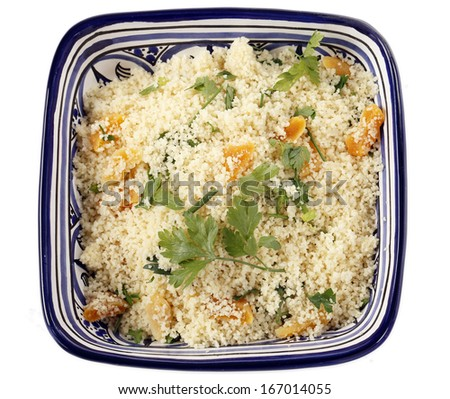 couscous mixed with chopped dried apricots and fresh parsley in a blue and white bowl - stock photo