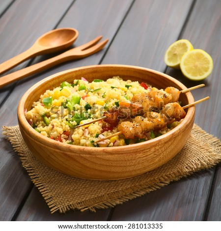 Couscous salad with bell pepper, tomato, cucumber, red onion, sweet corn kernels with baked chicken on skewer. Photographed on dark wood with natural light (Selective Focus, Focus one third into dish) - stock photo
