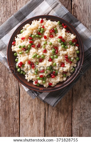Couscous salad with green peas and pomegranate on the table. vertical top view - stock photo