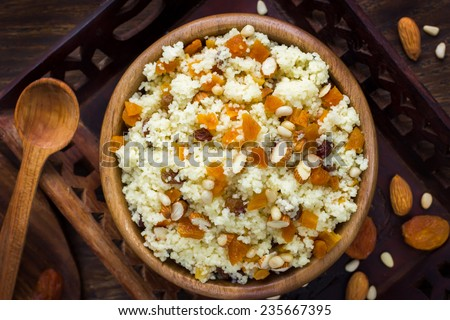 Couscous with dried fruits and nuts, top view - stock photo