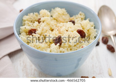 couscous with dry fruits on blue bowl on wooden background