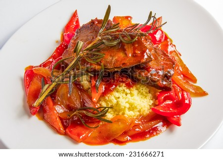 couscous with lamb in sweet and sour tomato sauce with carrot, onion and sweet pepper on white plate - stock photo