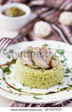 Couscous with pesto sauce, fried sliced pork, tasty dish, beautiful presentation - stock photo