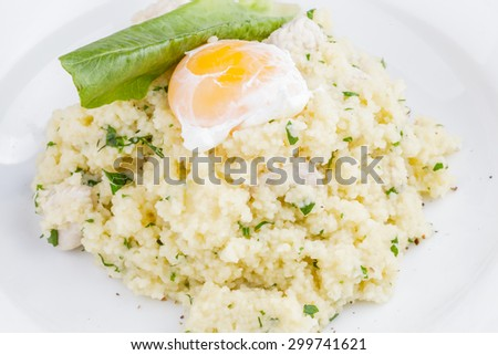 Couscous with poached egg and turkey - stock photo