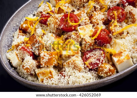 Couscous with roasted pumpkin, tomatoes and grilled halloumi cheese, topped by orange zest. - stock photo