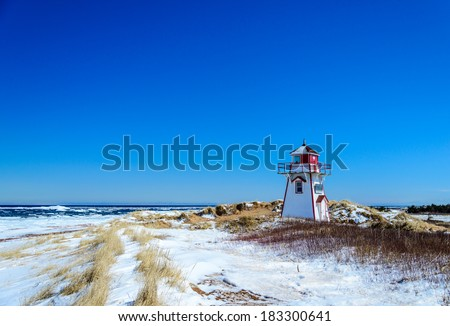Covehead PEI lighthouse in winter, ice breaking up in Atlantic - stock photo