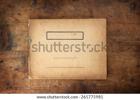 Cover of old 1950s - 1960s sketchbook or scrapbook on old well used wooden table or desk.  - stock photo