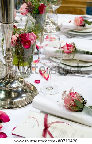 Covered banquet with red roses decoration - stock photo