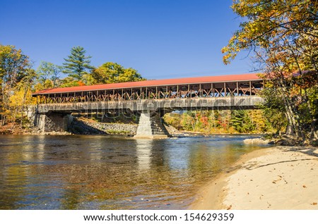 Covered Bridge in Autumn and Reflection in Water - stock photo
