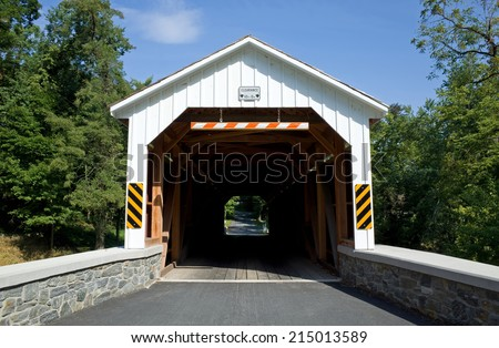 Covered bridge in Lancaster County, PA.  A covered bridge is a timber-truss bridge with a roof and siding which, in most covered bridges, create an almost complete enclosure. - stock photo