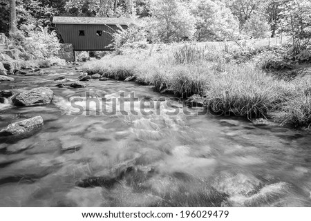 covered bridge over a brook in monochrome - stock photo