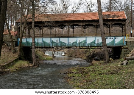 Covered bridge over the river with a small waterfall - stock photo