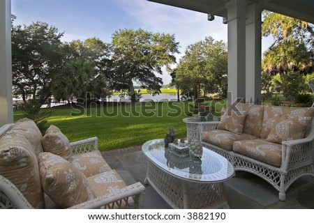 covered patio looking out onto waterfront property - stock photo