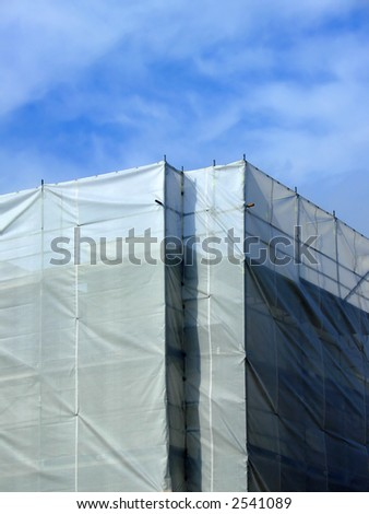Covered scaffolding around a highrise building - stock photo